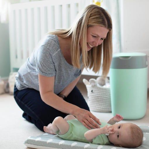 mum-changing-baby-nappy-on-changing-mat-in-nursery