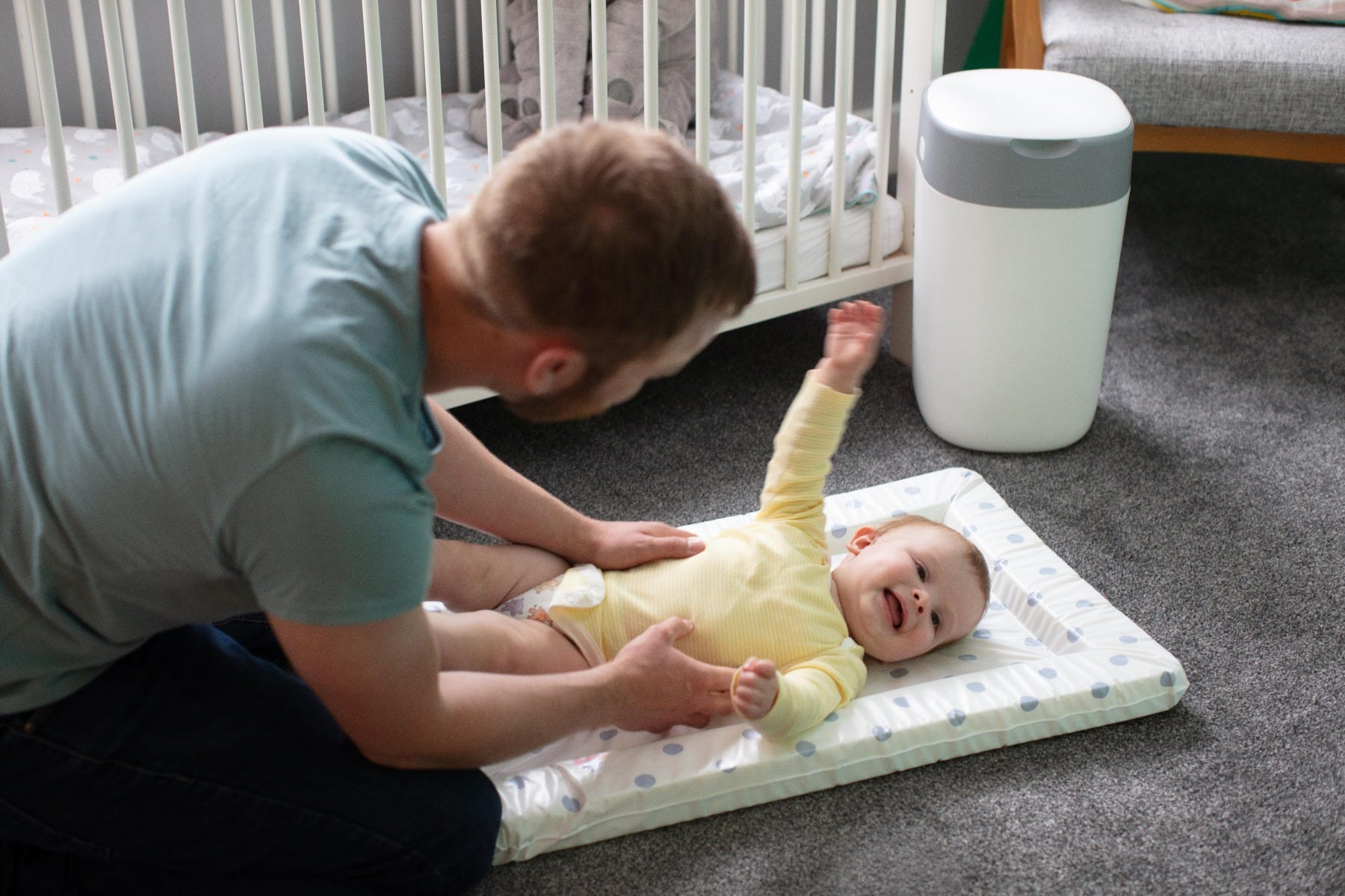 man-changing-baby-nappy-on-floor-in-nursery-whit-white-twist-and-click-in-background