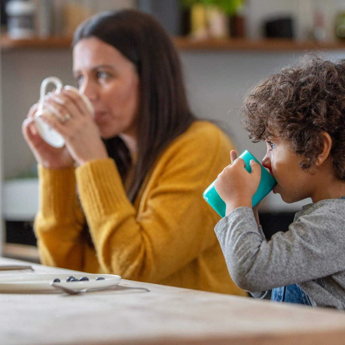 toddler-drinking-from-green-Easiflow-360°-Cup-with-handles-next-to-mum-drinking-from-mug-at-dinner-table