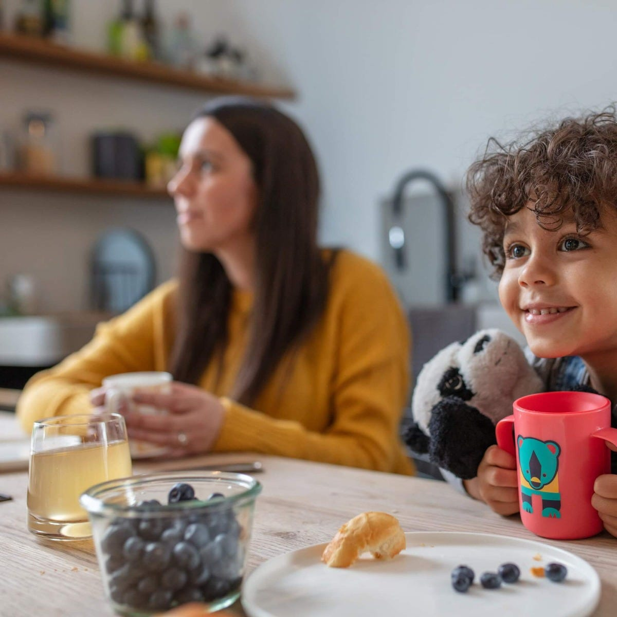 toddler-smiling-holding-pink-Easiflow-360°-Cup-with-handles-and-bear-design-next-mum-at-breakfast