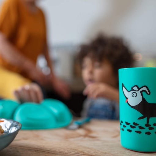 green-no-knock-cup-with-dog-design-and-blurred-background-of-boy-and-mum-in-kitchen