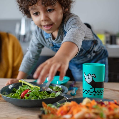 little-boy-at-dinner-table-reaching-over-green-dog-no-knock-cup-to-serve-himself