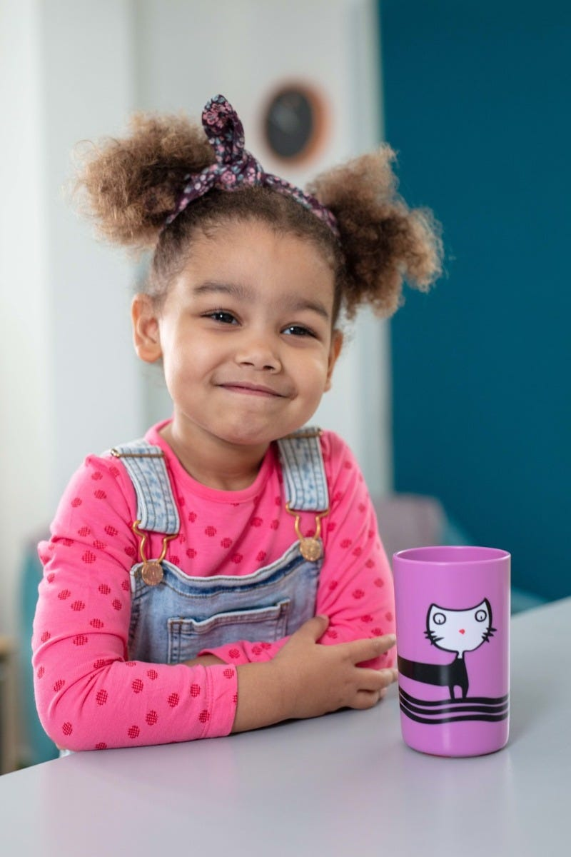 little-girl-smiling-next-to-purple-no-knock-cup