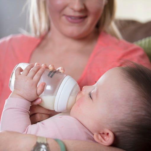 mum feeding baby with glass bottle