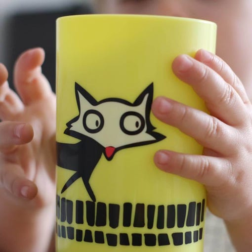 small-toddler-hands-holding-yellow-no-knock-cup-with-fox-design-close-up