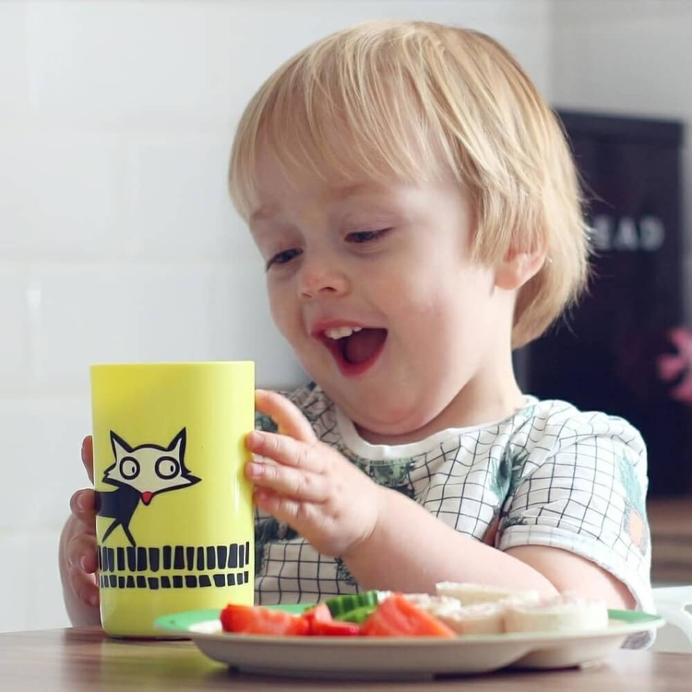 toddler-sitting-at-dinner-table-easily-picking-up-large-yellow-no-knock-cup-and-admiring-fox-design