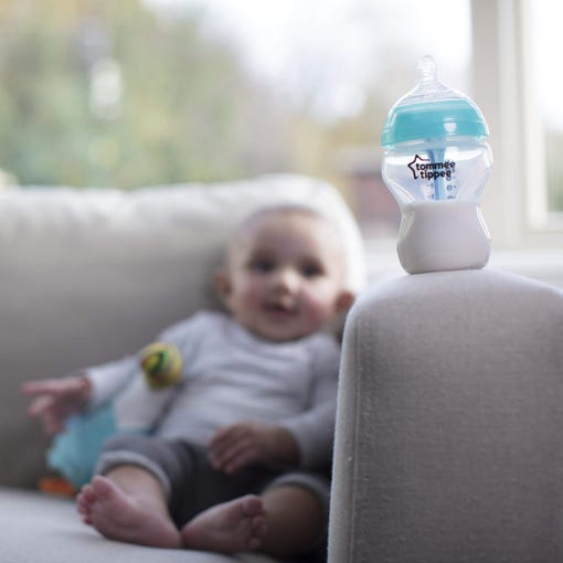advanced anti-colic baby bottle on sofa with baby in background