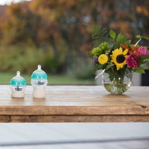 Advanced Anti Colic Bottle, turquoise, with milk, wood work top counter
