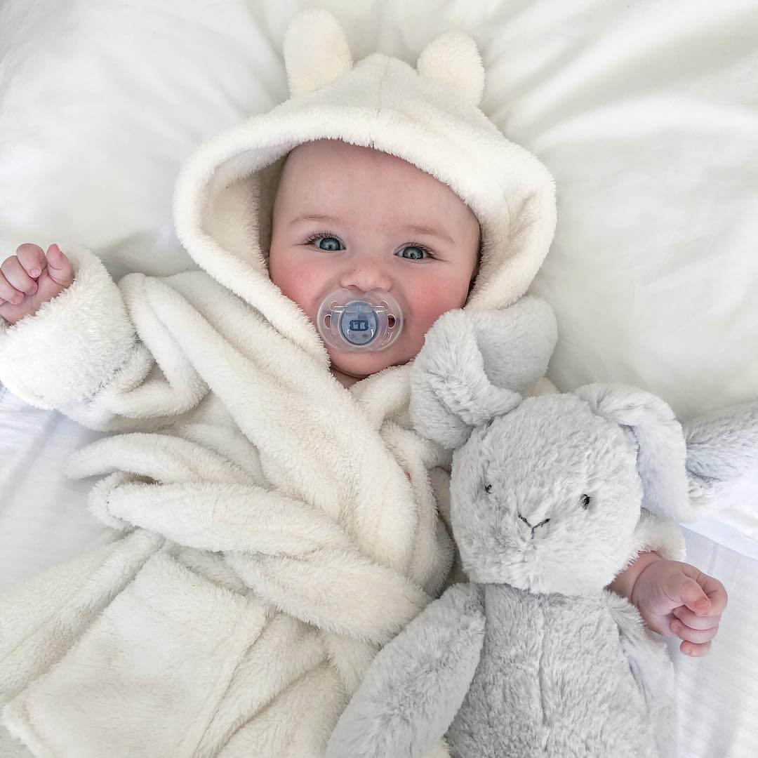 baby-in-dressing-gown-with-fun-style-soother-in-mouth