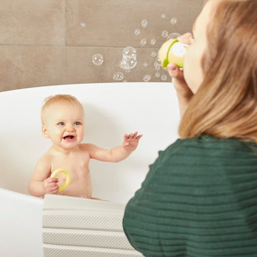 baby laughing while mum is blowing bubbles