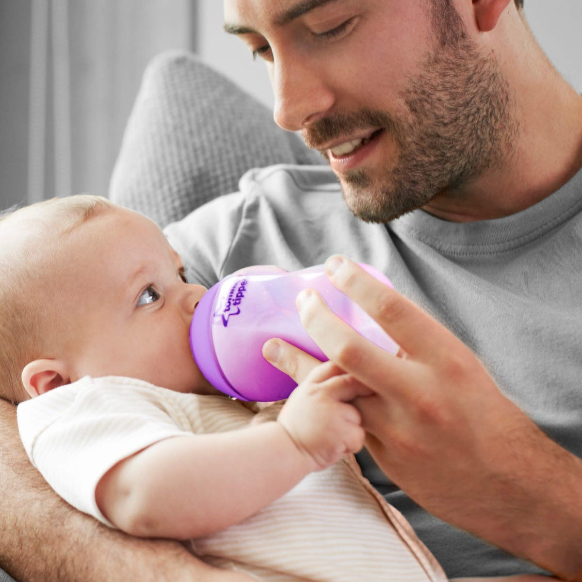 Dad feeding baby with Tommee Tippee bottle filled with milk
