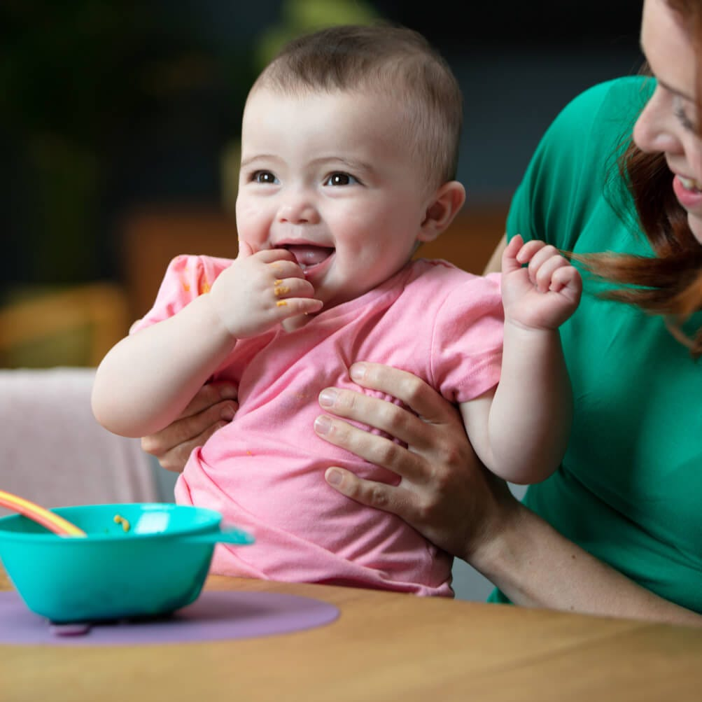 easy-scoop-feeding-bowl-blue-heat-sensing-spoon-orange-magic-mat-purple-mum-holding-baby-baby-looking-away-indoors