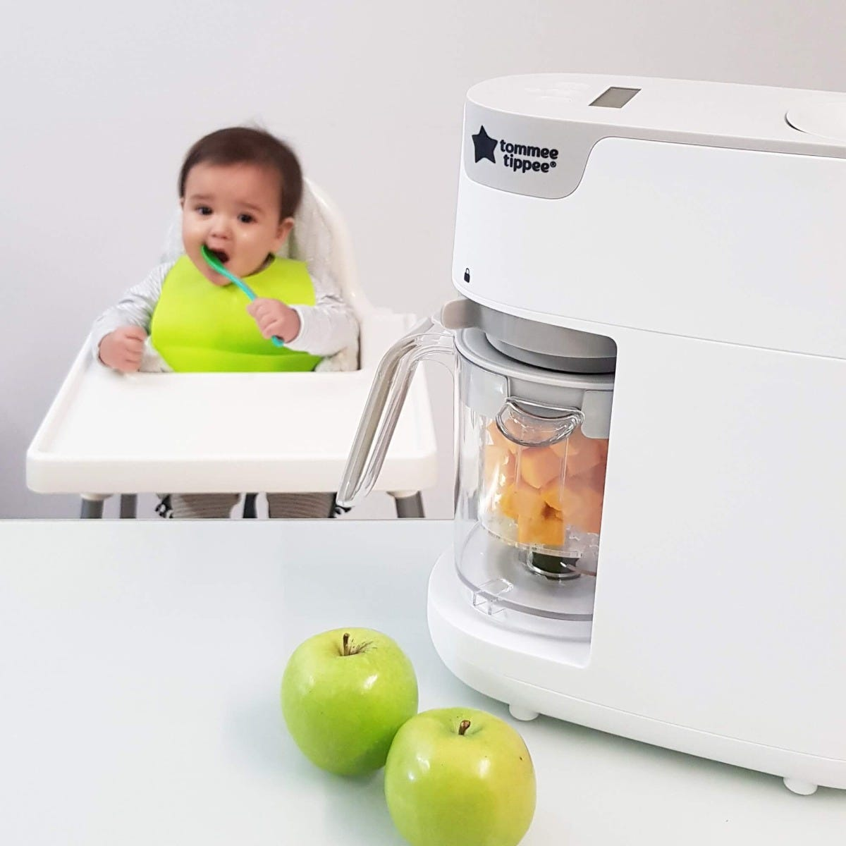 white-Quick-Cook-Baby-Food-Maker-containing-chopped-vegetables-and-baby-in-background-in-highchair