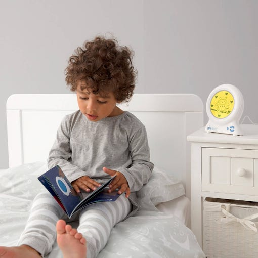 boy-sitting-on-bed-reading-groclock-book