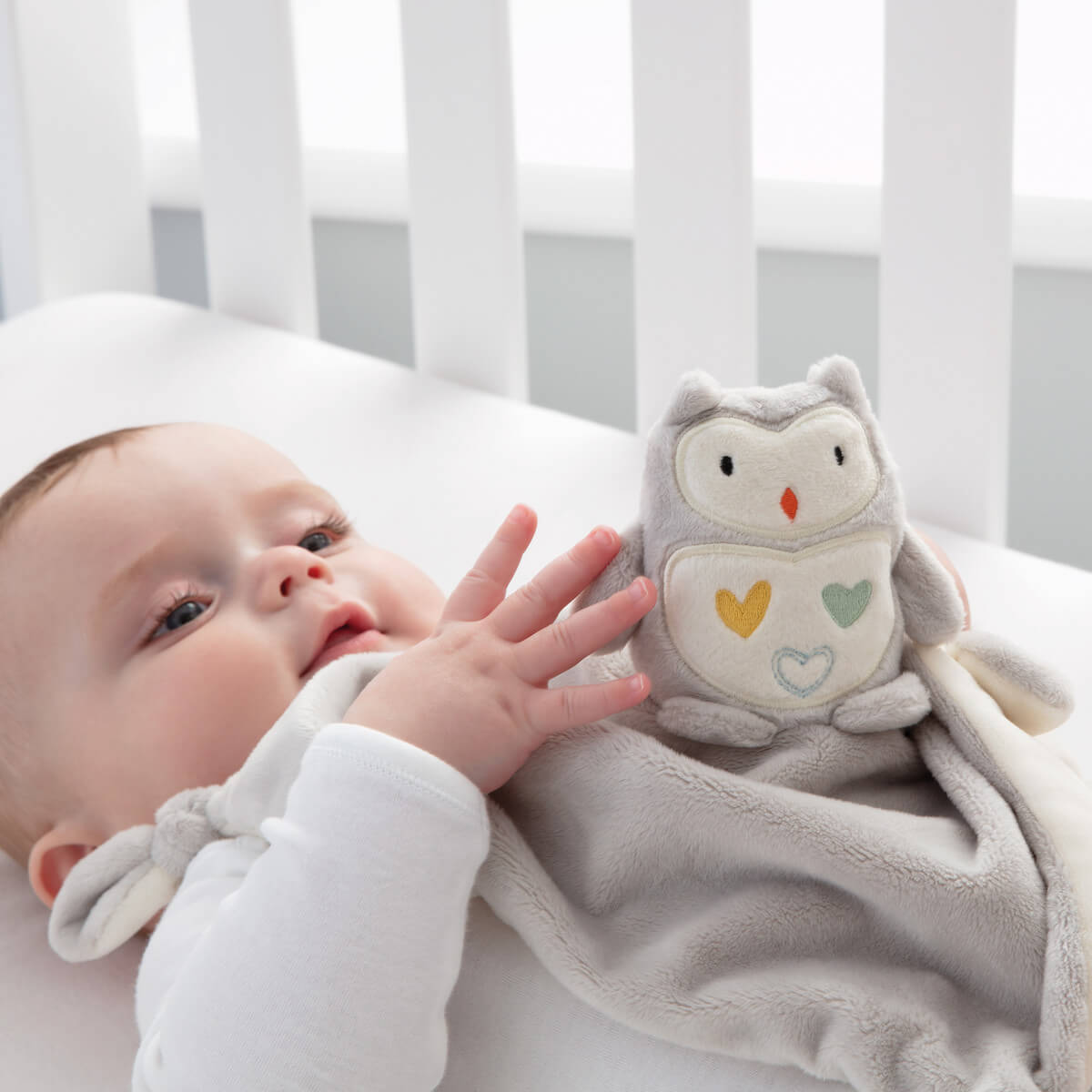 baby-in-cot-playing-with-ollie-the-owl-comforter