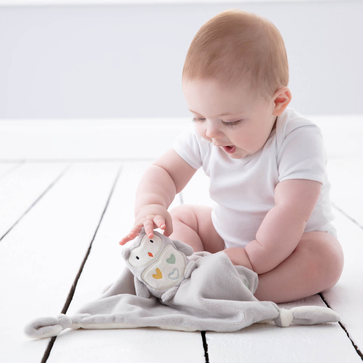 baby-playing-with-ollie-the-owl-gro-comforter
