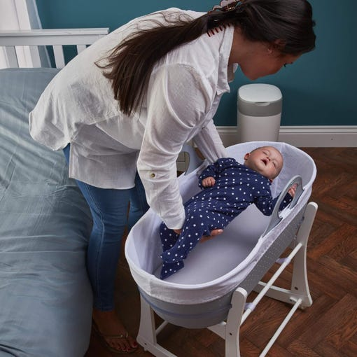 Mother putting baby into sleepee moses basket