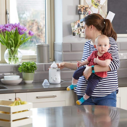 mum-in-kitchen-holding-baby-whilst-using-easi-warm-food-and-bottle-warmer-that-is-on-kitchen-bench