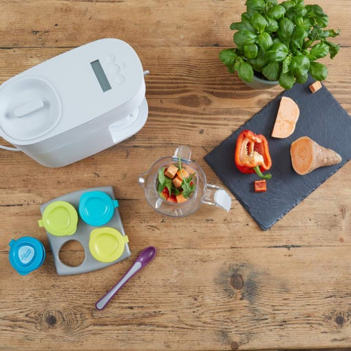 white-Quick-Cook-Baby-Food-Maker-steamer-blender-top-down-shot-on-bench-with-pop-up-freezer-trays-pots-and-tray-and-ingredients-including-sweet-potato-basil-and-red-pepper