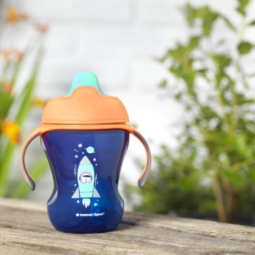 royal-blue-space-kid-sippee-cup-with-space-kid-design-on-garden-bench