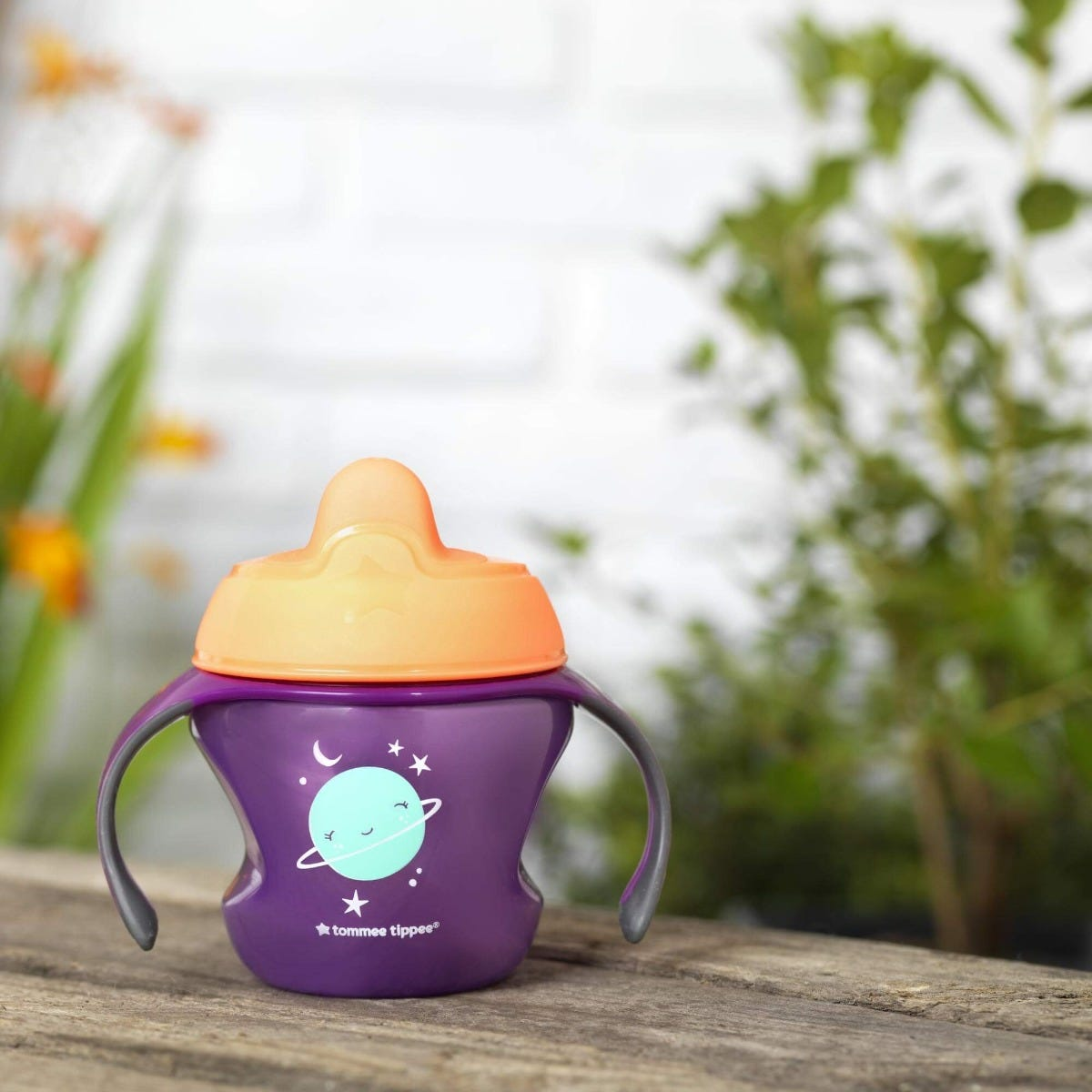 purple-first-sippee-cup-with-orange-soft-spout-on-garden-bench