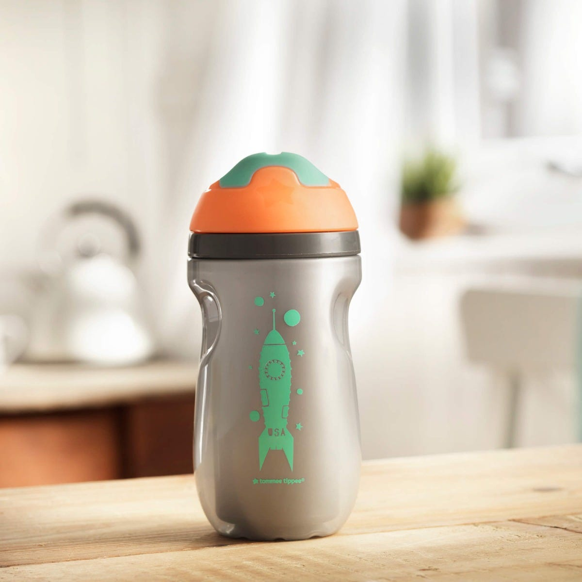 Insulated-sippee-cup-in-silver-with-orange-cap-and-aqua-spout-with-an-aqua-blue-rocket-design-sitting-on-kitchen-bench