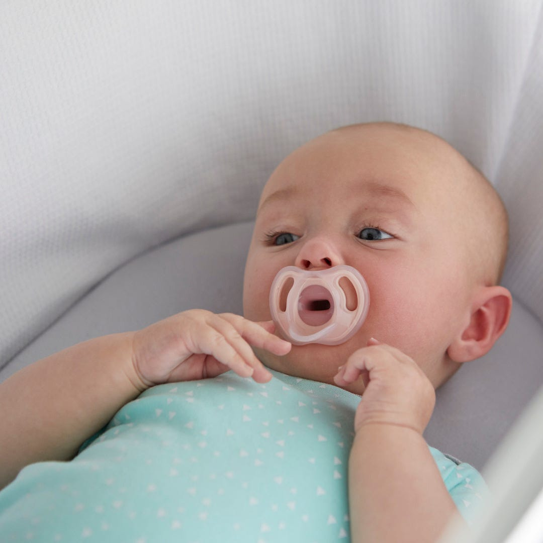 baby in moses basket holding Ultra-light pacifier