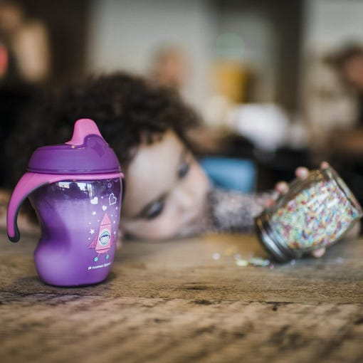 Space-girl-purple-pink-sippee-cup-on-kitchen-bench-with-toddler-playing-in-background