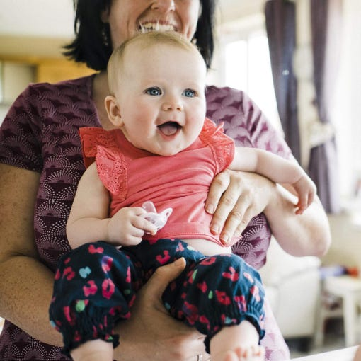 baby-smiling-whilst-holding-moda-soother